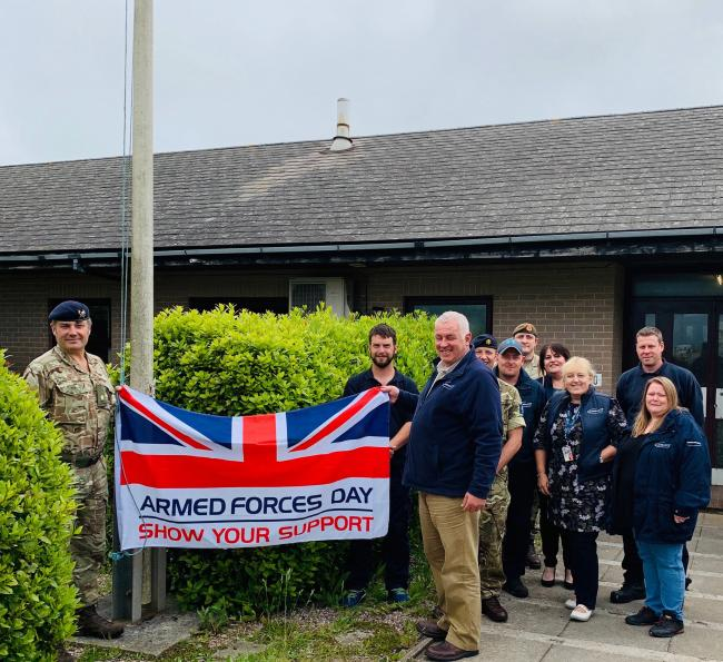 Pictured: Major John Poole – (holding flag) Senior Training Safety Officer – DIO; Richard Incledon – (holding flag) Area Delivery Manager – Landmarc; Rob Foster-James – Training Area Operative – Landmarc; WO1 (RSM) Wayn