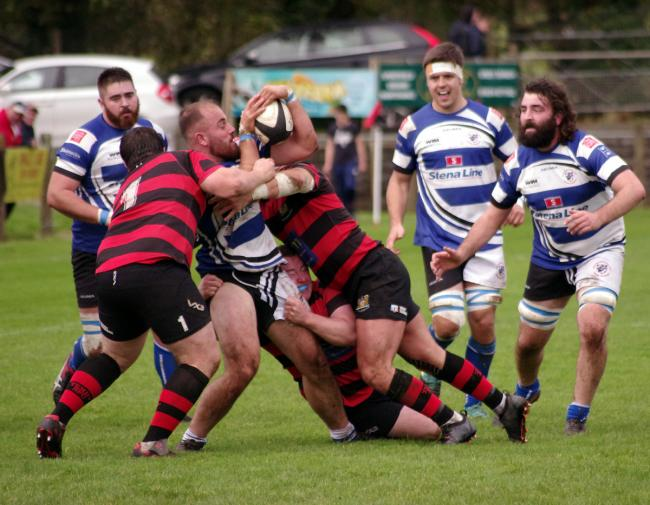 Fishguard skipper Chris Shousha takes a hit in midfield. PICTURE: Western Telegraph.