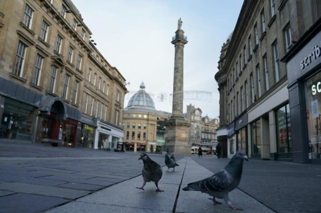Pigeons occupy empty streets near the Grey's Monument in Newcastle