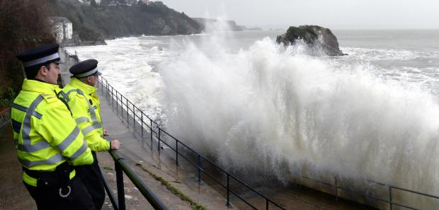 Milford Mercury: Splashing time: As waves crash over Tenby's North Walk on Monday morning, two PCSOs patrol the seafront to ensure the safety of any spectators. PICTURE: Gareth Davies Photography