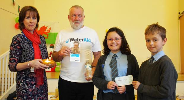 WATER GREAT EFFORT: Head girl Megan Rickard and head boy Tom Blockwell, pictured with headteacher Mrs Sue Roberts, present a cheque for £100 to Dave Padfield of Water Aid. PICTURE:Milford Mercury. (5033166)