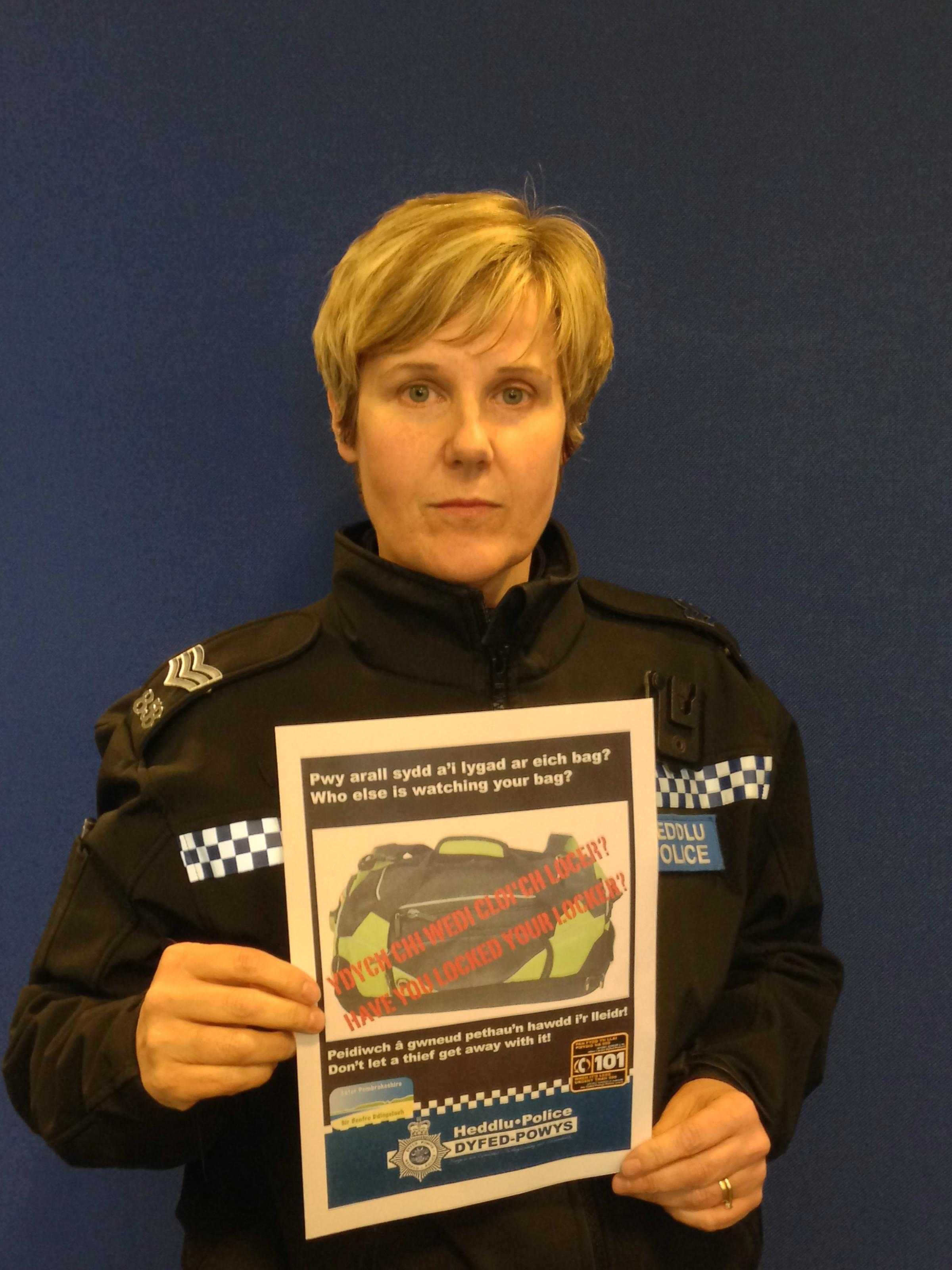 Sgt Catrin Thomas with a crime prevention poster.