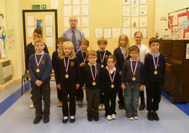 MEDALS: Pictured are the children who achieved 100 per cent attendance together with headteacher Mr Paul Harries. (5999260)