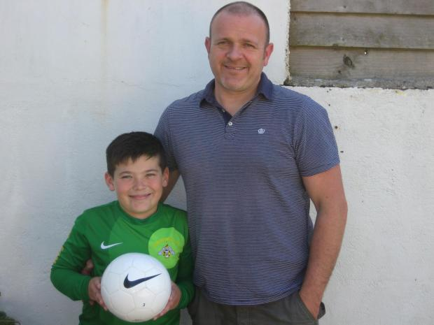 BRAZIL BOUND: Lucky Morgan James and his dad, Julian, are off to the World Cup, where the nine-year-old will escort the England team onto the pitch. PICTURE: Western Telegraph (6257434)