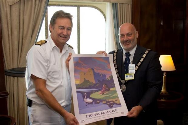 CRUISE CONTROLLER: Capt Rikard Lorentzen is presented with a set of retro posters promoting the national park by PCNPA chairman Cllr Mike James. (9427058)