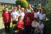 "GROW TEAM: Year 5 children pictured with their ""Buddy Bench"", gardening club leader Mrs Griffiths, Sue Lawton of the British Potato Council and representatives from Puffin Potatoes. (10708650)"