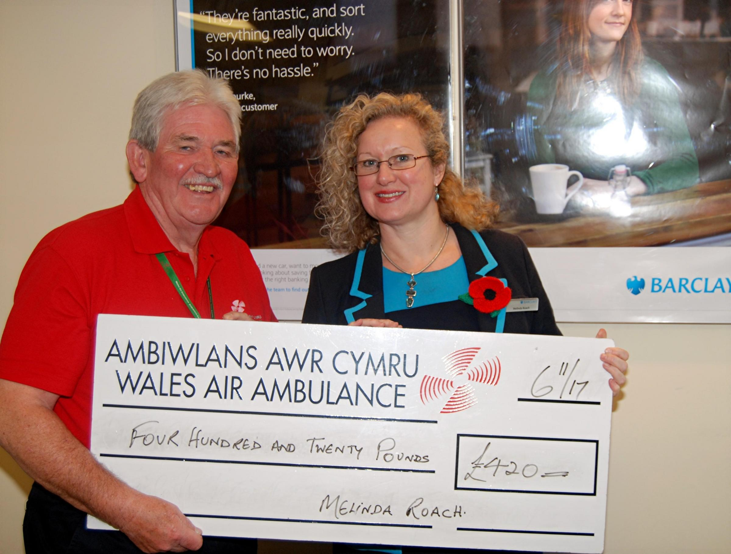 Melinda presents a cheque to the Wales Air Ambulance.