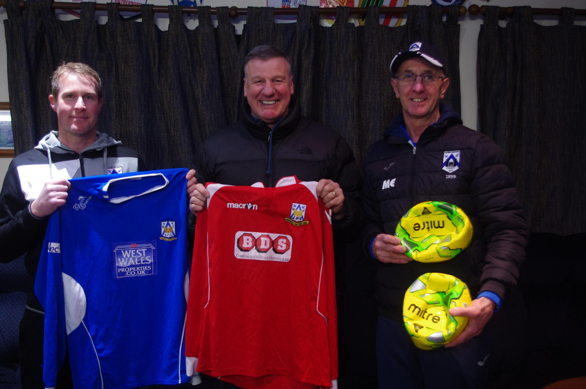 Bernie Armstrong (centre) receives football kit and balls from Haverfordwest County coaches Steve Batty (left) and Micky Ellis (right).