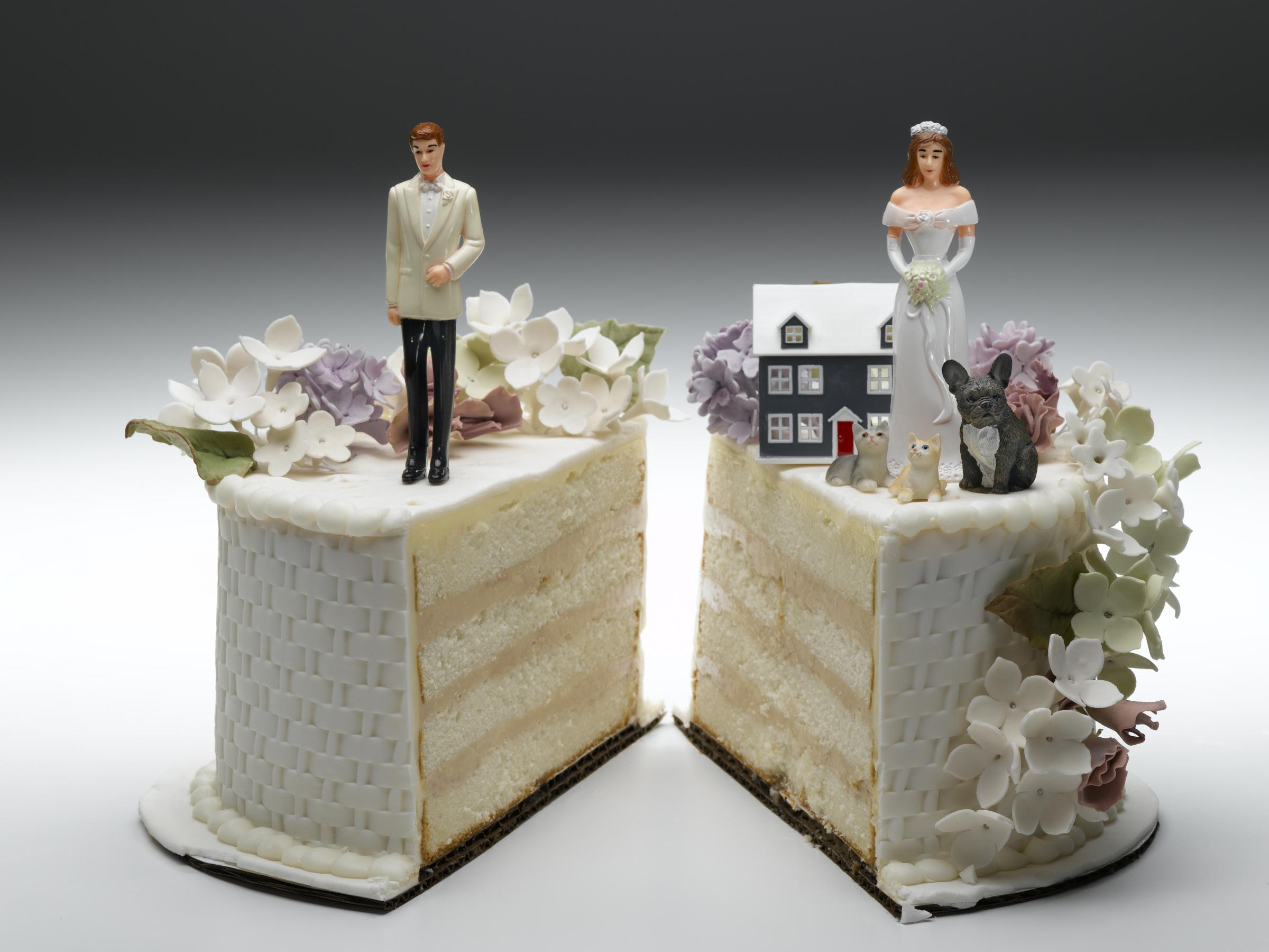 Divorce Bride and groom figurines standing on two separated slices of wedding cake.