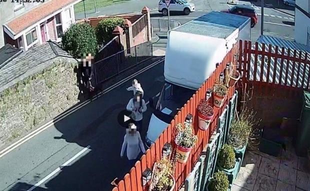 Milford Mercury: CCTV shows a young family having to walk in the middle of the road because a van is blocking the only pavement.