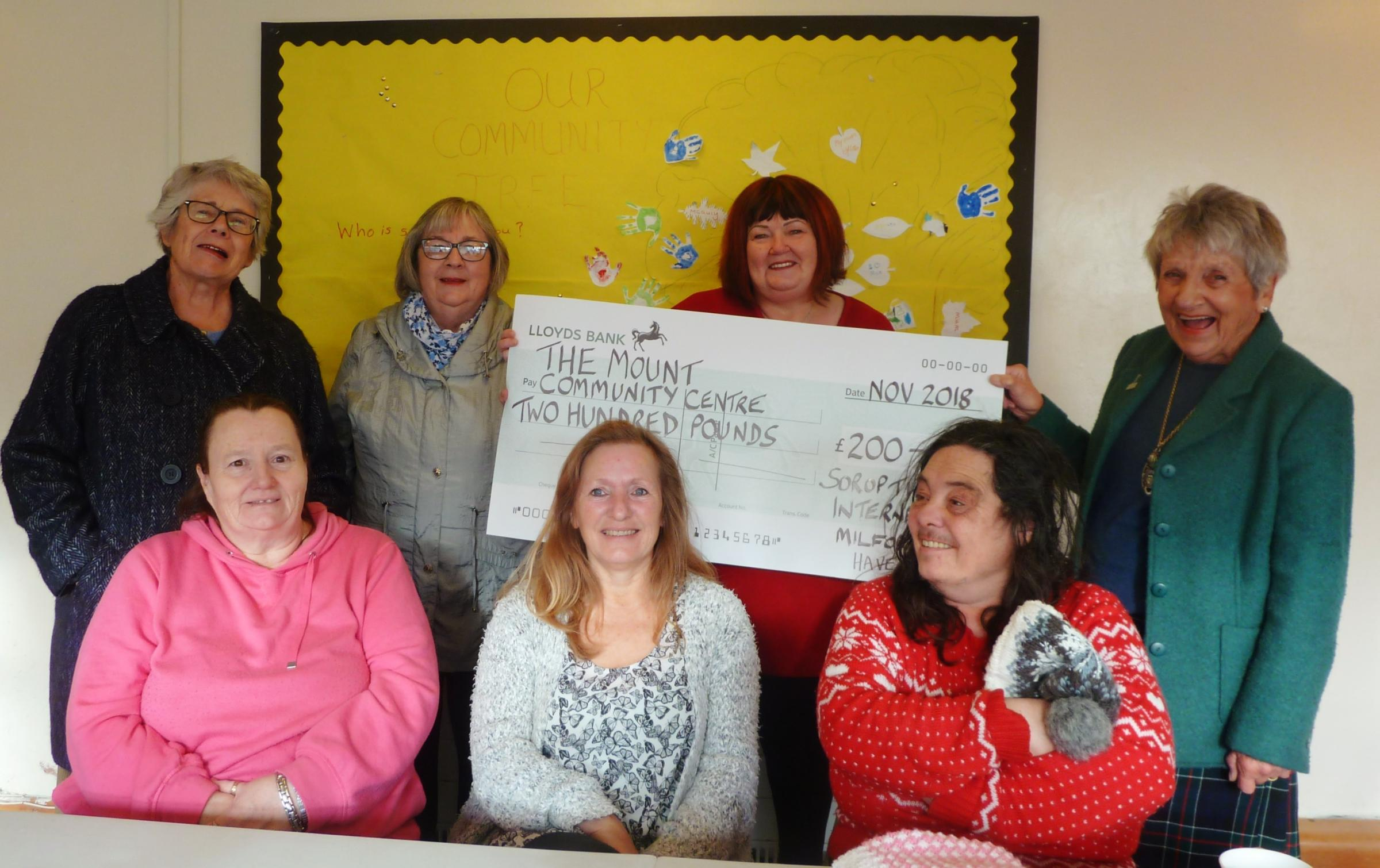 SI President Sarah Colquhoun is pictured presenting the cheque to charity trustee Lynne Turner, with members of SI Milford Haven and residents of the Mount estate.