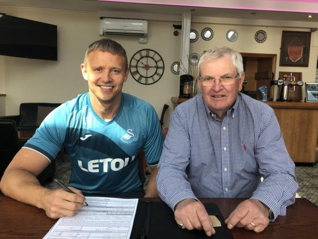 Lee Trundle signing for Haverfordwest in the summer, with Chairman David Hughes.
