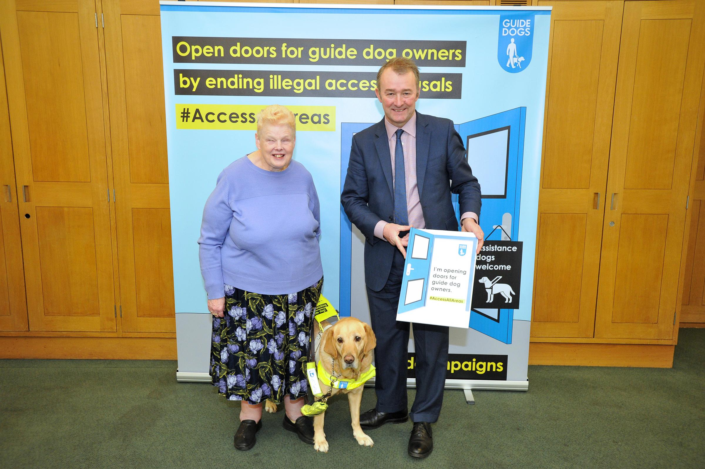 Simon Hart MP with June and guide dog Shannon helping to keep doors open for guide dogs.