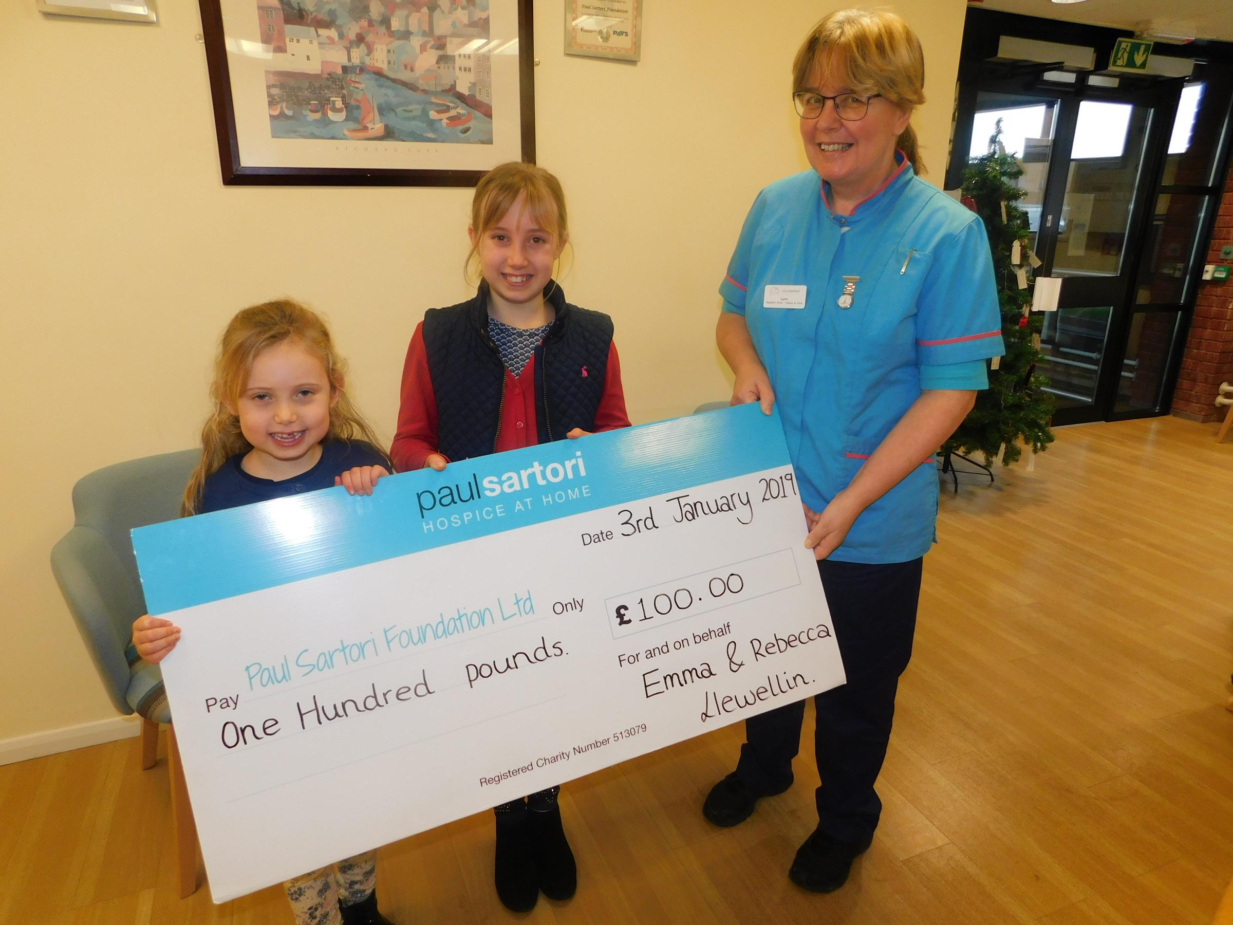 Pictured, from left: Emma and Rebecca Llewellin present their cheque to Lynn Hunter, Management RN at Paul Sartori Hospice at Home.